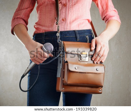 Female journalist with microphone. Retro style jeans and bag. - stock photo