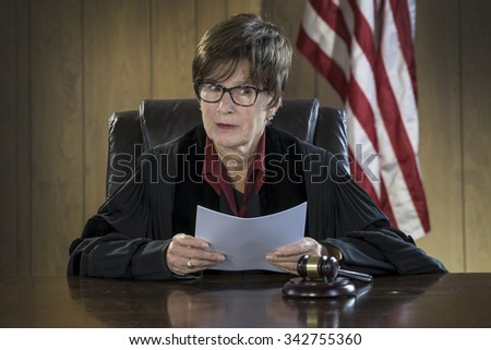 Female judge reading a verdict in a courtroom - stock photo
