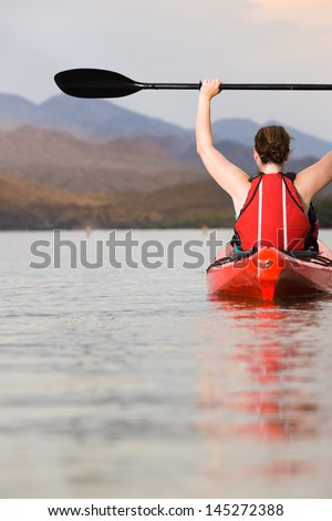 Female Kayaker with Arms and Paddle Raised Above Head - stock photo