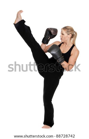 Female kick boxer doing a front kick isolated on a white background