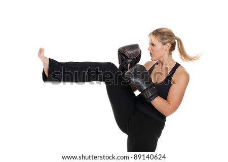 Female kickboxer kicking isolated on white - stock photo