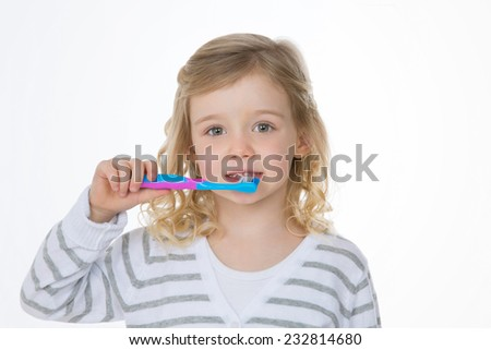 female kid washes her teeth with pink and blue toothbrush