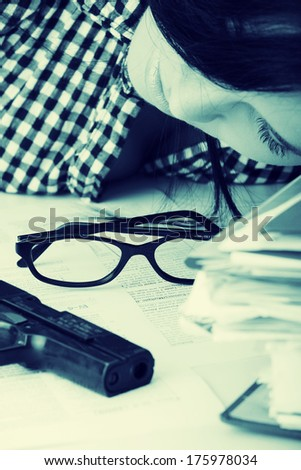 Female kild her self while filling out tax forms while sitting at her desk. - stock photo