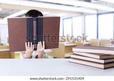 Female kindergarten school student reading textbooks in the class while covering her face - stock photo