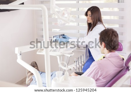 Female latin dentist showing some x-rays to a patient - stock photo