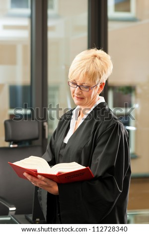 Female lawyer with German civil law code in a court room - stock photo