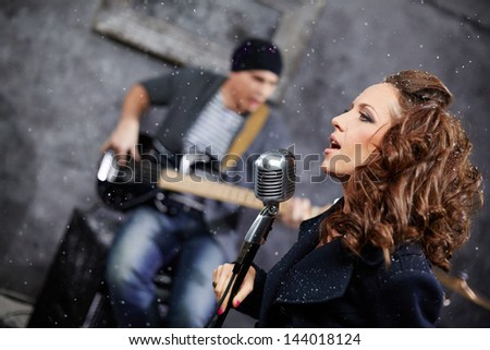Female lead vocalist and guitarist in studio, turned frame - stock photo