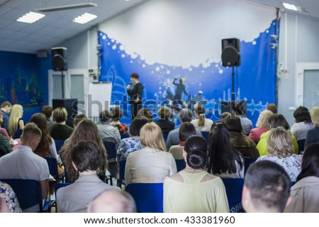 Female Leader Lecturer Speaking In front of the Large Group of People. Horizontal Image Composition - stock photo
