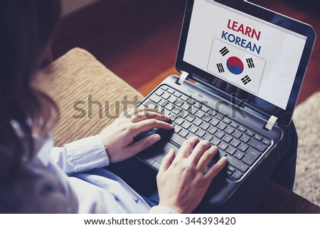 Female learning korean at home with a laptop computer at home. - stock photo