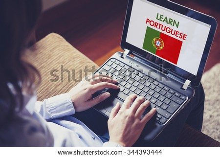 Female learning portuguese at home with a laptop computer at home. - stock photo