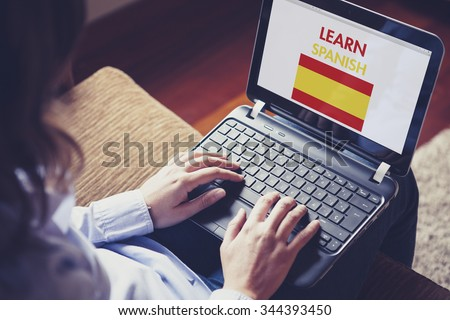 Female learning spanish at home with a laptop computer at home. - stock photo