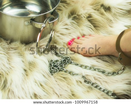 female leg chained to a saucepan: the concept of domestic slavery