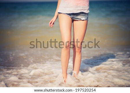 Female leg walking on the beach in the ocean.  - stock photo