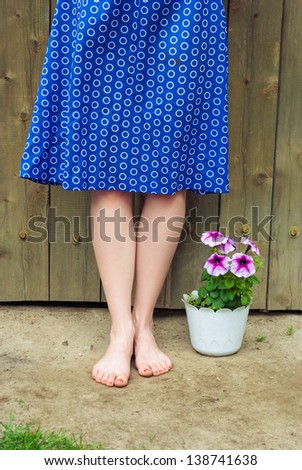 female legs against a wooden wall, next to the flowers in the pot. - stock photo