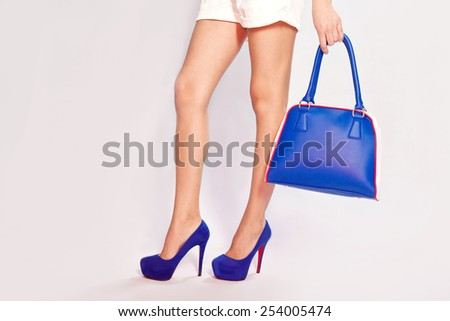 Female legs, blue shoes and bag - stock photo