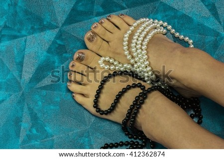 Female legs, decorated with beads - stock photo