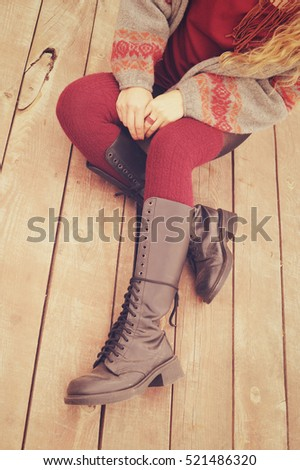 Female legs dressed in leather shoes with laces and knitted stockings, fashion jersey and hands with ring made from beads, woman sitting on a wooden planking, autumn outdoor fashion photo, warm colors