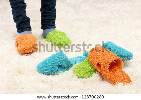 Female legs in color slippers, on carpet background - stock photo