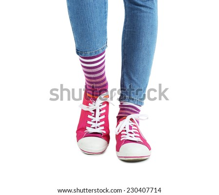 Female legs in colorful socks and sneakers isolated on white - stock photo