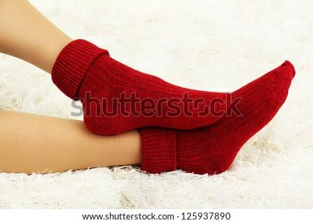 Female legs in colorful socks on  white carpet background - stock photo