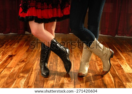 Female Legs in Cowboy Boots in a Line Dance Step on hardwood floor - stock photo