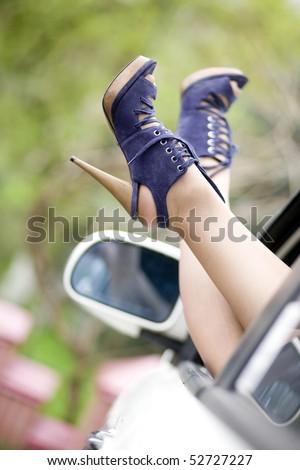Female legs in high heel shoes, car window - stock photo