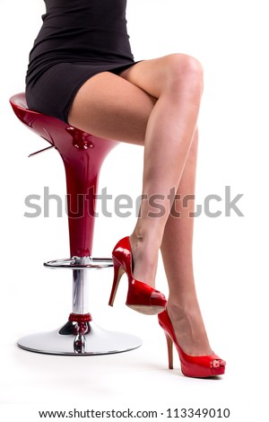 female legs in high heels sitting on chair - stock photo