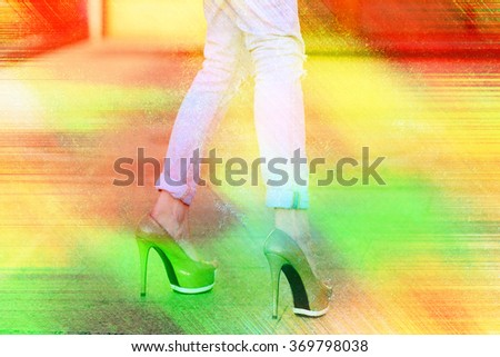 Female legs in jeans and heels against the bright rainbow colored background (double exposure) - stock photo