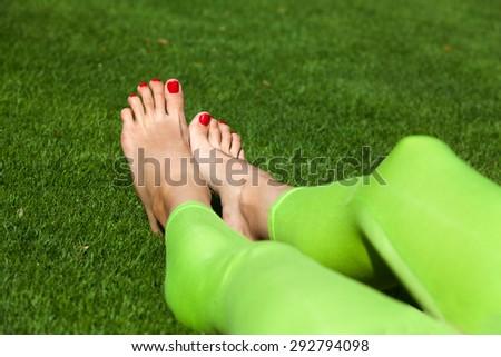 Female legs in leggings on green grass - stock photo