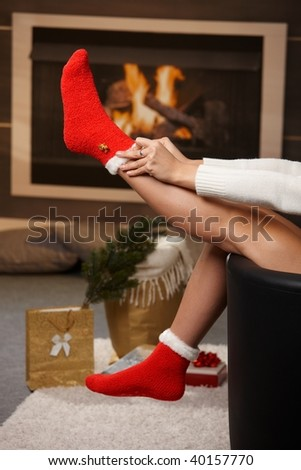 Female legs in santa claus socks at christmas in front of fireplace. Gifts on the floor. - stock photo