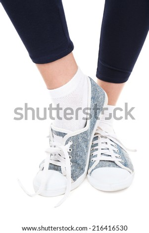 Female legs in sneakers isolated on white - stock photo