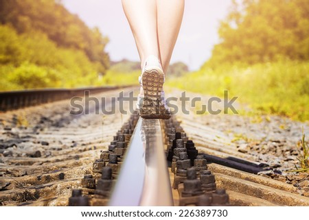 female legs in sneakers on the rail of the railway - stock photo
