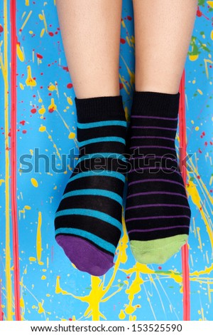 female legs in  striped socks over colorful ink splashes wall - stock photo