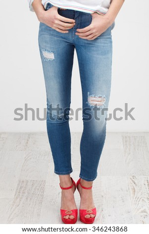 Female legs in the blue jeans on white background