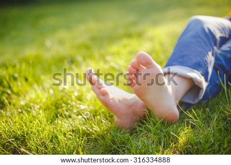 female legs lie on the grass on a sunny day - stock photo