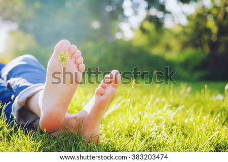 female legs lie on the grass with spring flower on sunny day  - stock photo