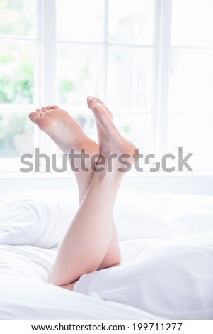 Female legs lying on bed at home in the bedroom