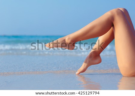 Female legs on blue sea background, side view