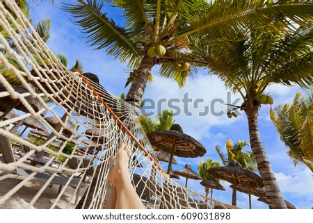 Female legs on hammock on tropical beach. Luxurious five stars holiday resort on Mauritius.