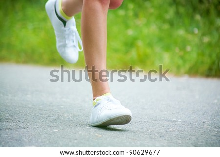 Female legs running on the road - stock photo