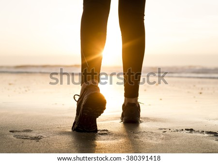 Female legs walking at the beach in direction to the sun - stock photo