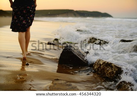 Female legs walking on the beach on a warm summer evening. - stock photo