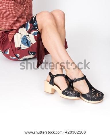 Female Legs Wearing Black Wooden Heel Sandals - stock photo
