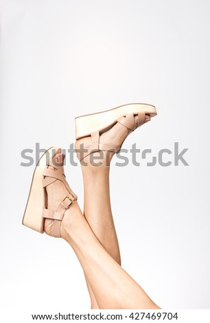 Female Legs Wearing Light Colored Leather Wedge Sandals - stock photo