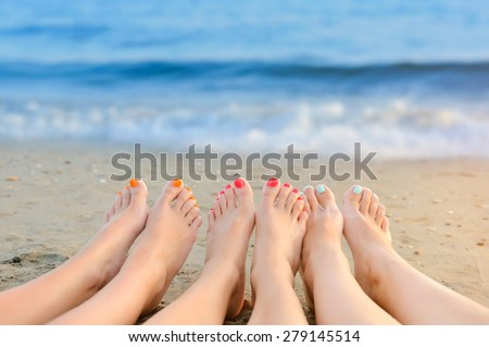 Female legs with color pedicure on the background of the sea - stock photo