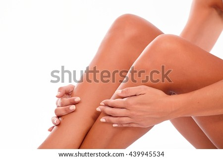 Female legs with knees bent holding flat palmed hands on calves on a white background