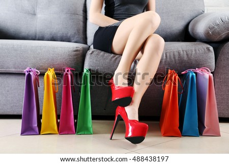 Female legs with red high heels and shopping bags on grey sofa