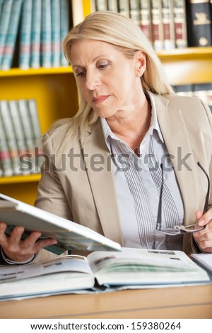 Female librarian holding glasses while reading book at table in college library - stock photo