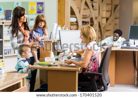 Female librarian scanning books while family standing at checkout counter in library - stock photo