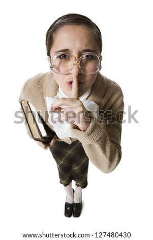 Female librarian with eyeglasses and books hushing - stock photo